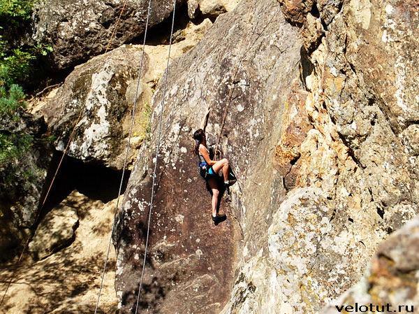 девушка лезет по скале