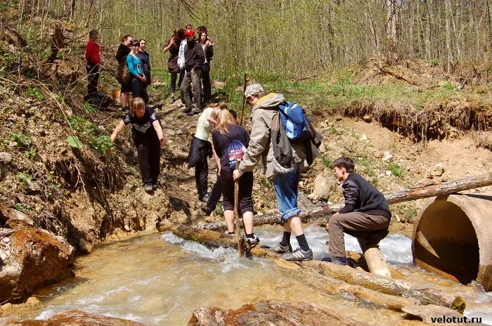 группа туристов переходит ручей