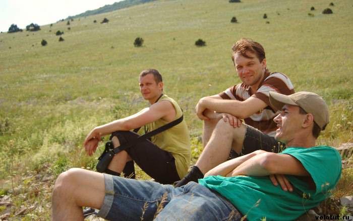 три туриста на зеленой траве