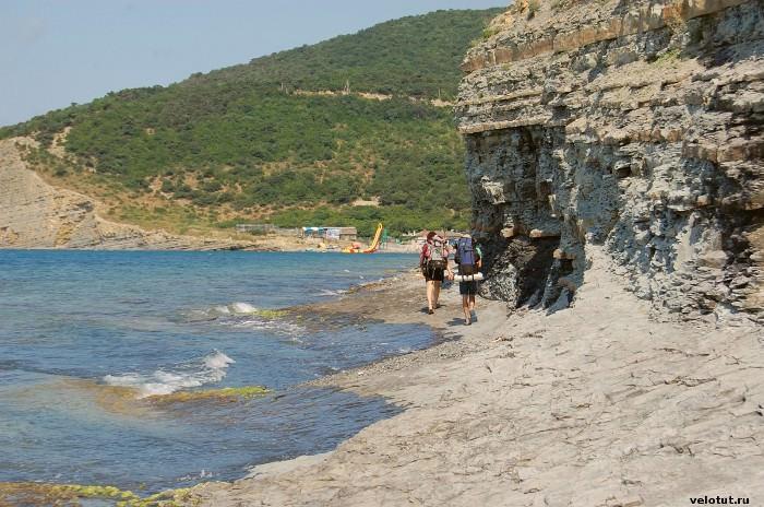 туристы идут по пляжу