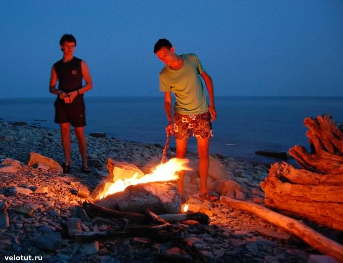 туристы разводят костер на море