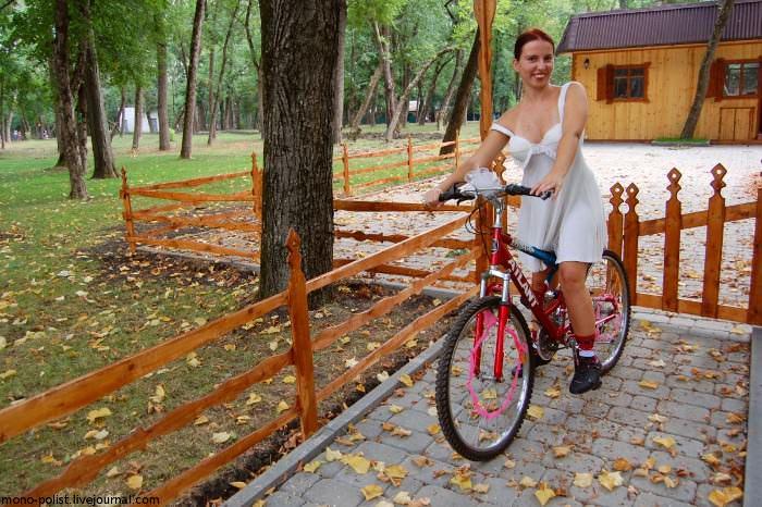 велосипедистка в белом платье на велосипеде