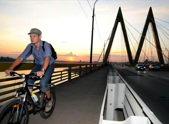 велосипедист едет по мосту Миллениум в Казани