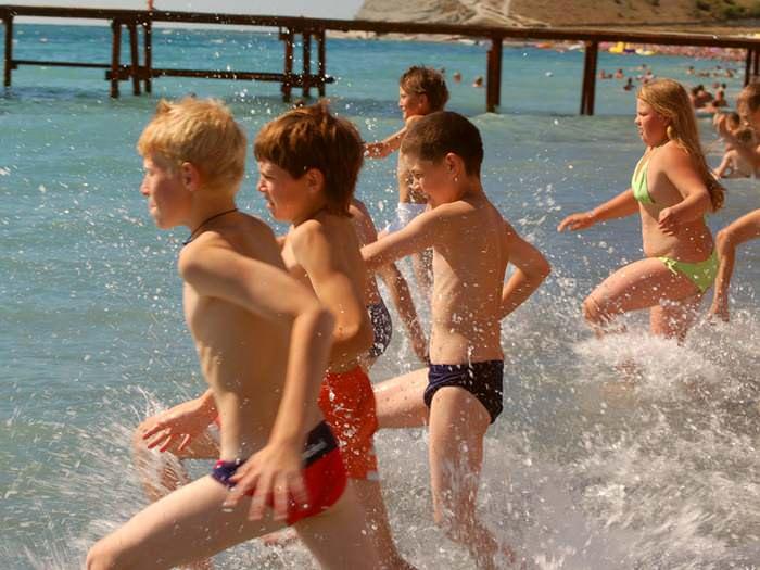 дети бегут в море