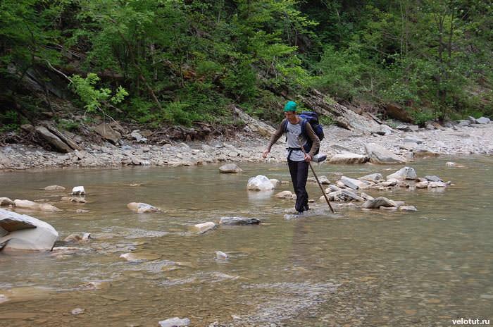 турист переходит реку вброд