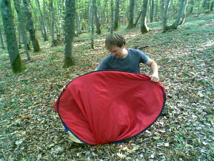 турист складывает палатку
